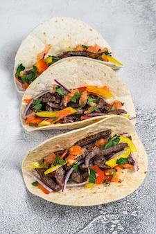 Mexikanische tacos mit rindfleisch, zwiebeln und paprika. weißer hintergrund. draufsicht.