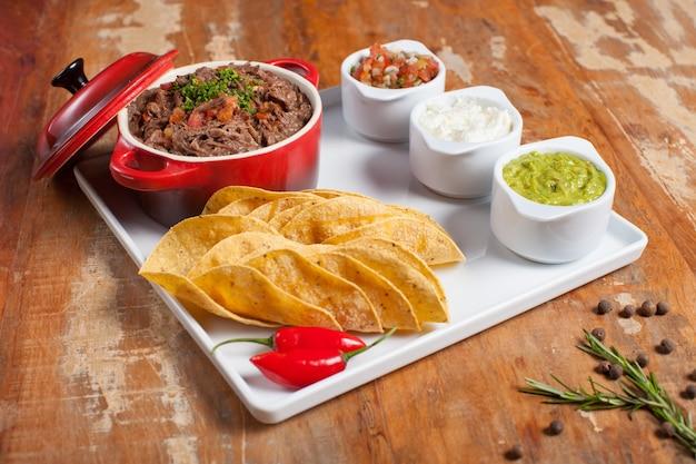 Mexikanische tacos mit zerkleinertem fleisch guacamole, saurer sahne, tomatensauce, salsa und glühenden chilischoten auf holztisch