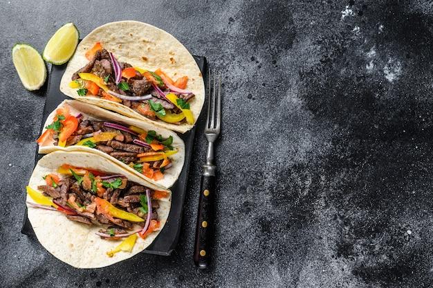 Mexikanische tacos muscheln mit rindfleisch, zwiebeln, tomaten und paprika. schwarzer hintergrund. draufsicht. speicherplatz kopieren.