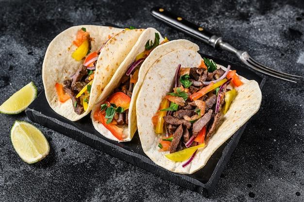 Mexikanische tacos muscheln mit rindfleisch, zwiebeln, tomaten und paprika. schwarzer hintergrund. draufsicht.