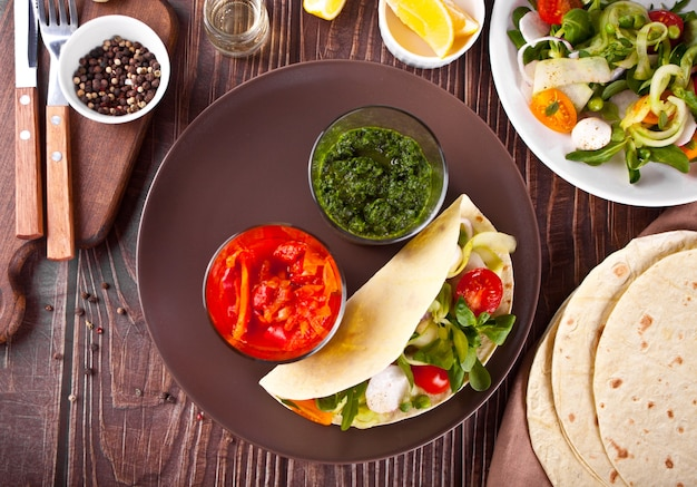 Mexikanische vegane tortilla wrap fladenbrot mit gemüse und saucendips auf dem esstisch