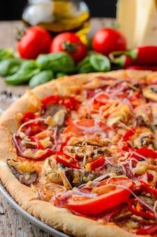Mexikanische würzige pizza und bestandteile auf einem holztisch. traditionelle italienische küche. partyessen