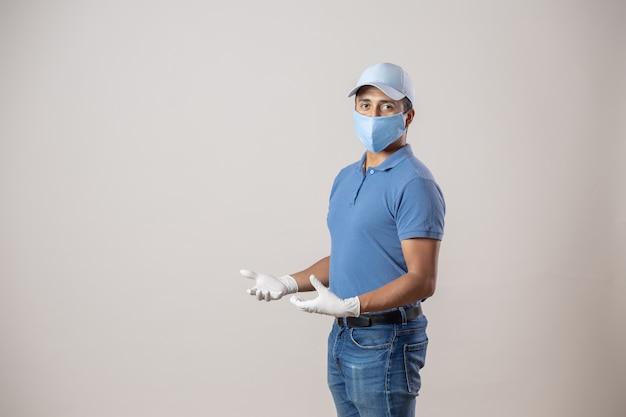 Mexikanischer bote, der handschuhe und gesichtsmaske auf grauer wand isoliert trägt