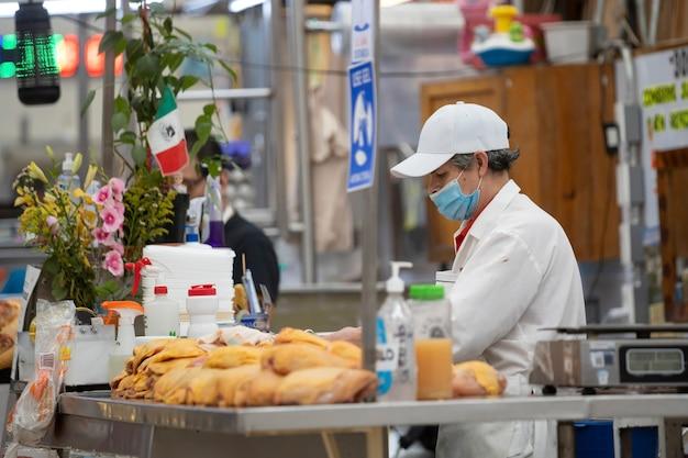 Mexikanischer geflügelladen, mann, der gesichtsmaske trägt, rohes huhn auf pupillenmarkt in mexiko schneidend