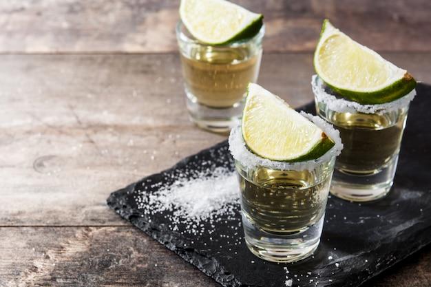 Mexikanischer goldtequila im glas mit limette und salz auf holztisch