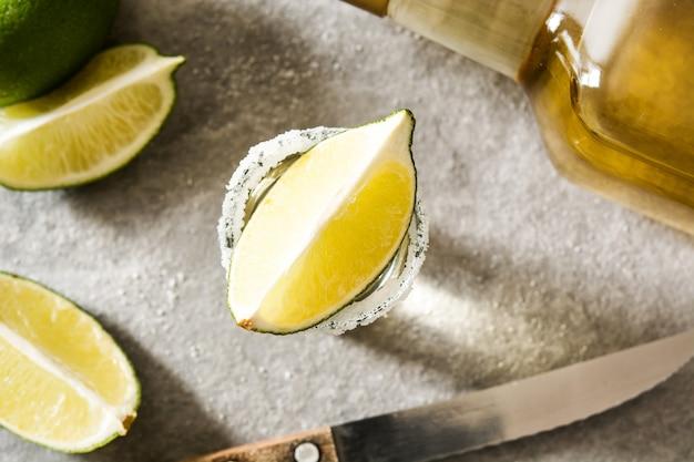 Mexikanischer goldtequila mit kalk und salz auf grauer hintergrundoberansicht