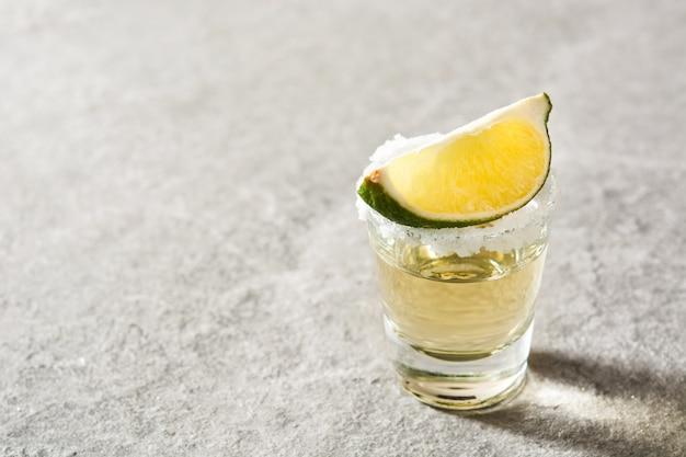 Mexikanischer goldtequila mit limette und salz auf grauem hintergrund mit kopienraum