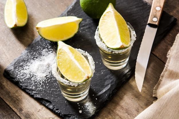 Mexikanischer goldtequila mit limette und salz auf holztisch
