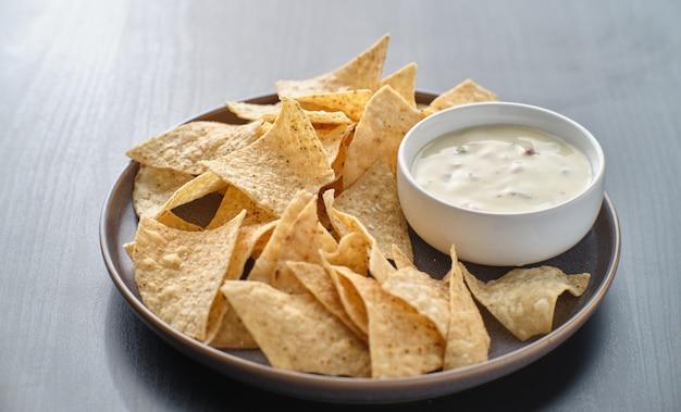 Mexikanischer heißer queso blanco-käsedip mit maistortillachips auf teller