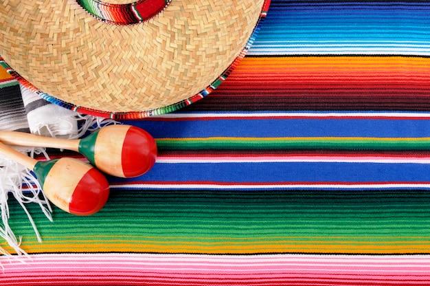 Mexikanischer hintergrund mit traditioneller decke und sombrero