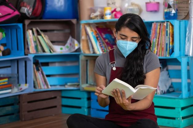 Mexikanischer junger lehrer, der ein buch auf einem leeren klassenzimmer liest