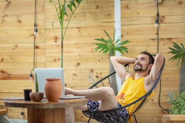 Mexikanischer junger mann, der an konzept der finanziellen freiheit der sommerferien arbeitet