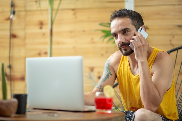 Mexikanischer junger mann, der an telefonanrufen im sommerurlaub arbeitet working