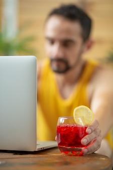 Mexikanischer junger mann, der im sommerurlaub arbeitet und einen cocktail trinkt