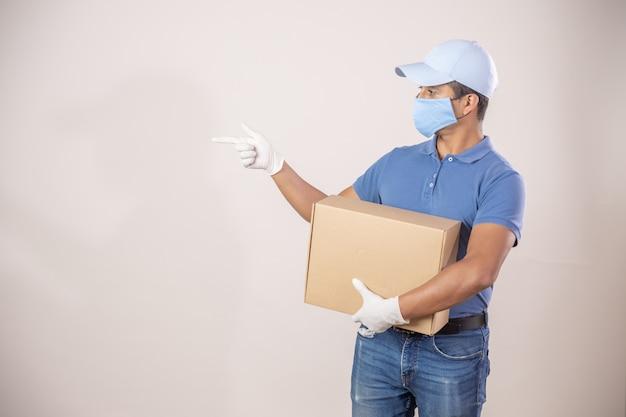 Mexikanischer kurier mit schutz gegen coronavirus-pandemie, der eine kiste zeigt und trägt