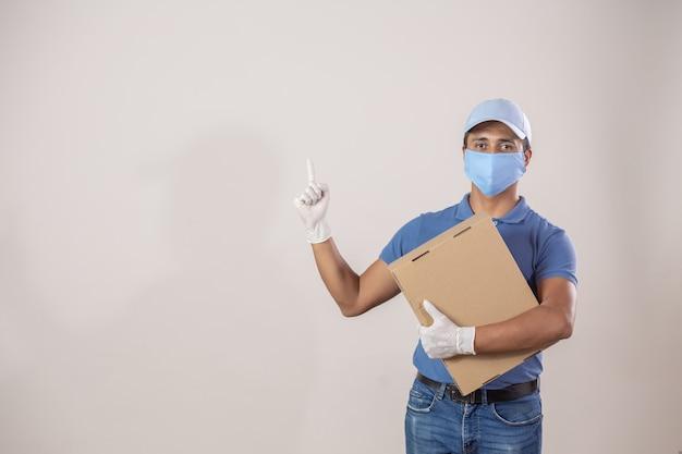 Mexikanischer kurier mit schutz gegen coronavirus-pandemie, der einen finger nach oben trägt