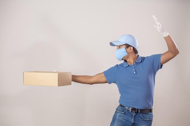 Mexikanischer kurier mit schutz gegen coronavirus-pandemie, der einen karton hält