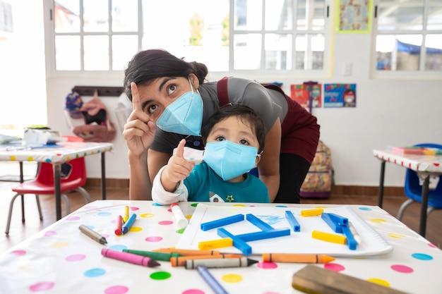 Mexikanischer lehrer und kind mit masken in der schule nach covid-19-quarantäne