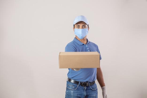 Mexikanischer lieferbote mit gesichtsmaske und handschuhen, die kartonpaket geben