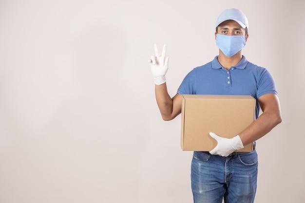 : mexikanischer lieferbote mit schutz gegen coronavirus-pandemie, der friedenszeichen tut, das einen pappkarton hält
