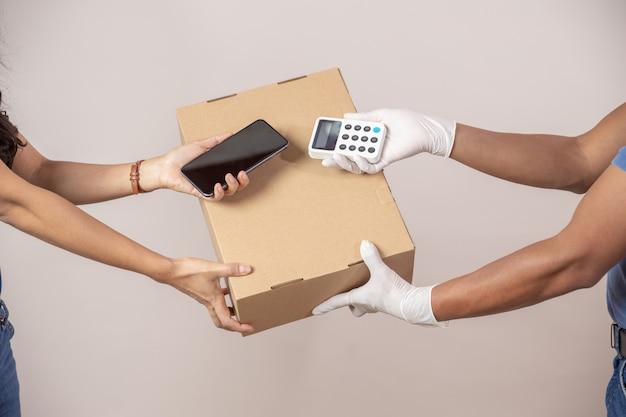 Mexikanischer lieferbote und -frau, die telefonzahlung tun