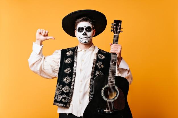 Mexikanischer mann mit hut zeigt mit dem finger auf die gitarre. schnappschuss des kerls im traditionellen kleid mit gesichtskunst auf isolierter wand.