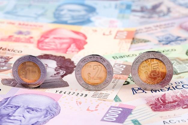 Mexikanischer peso prägt auf dem hintergrund von banknoten