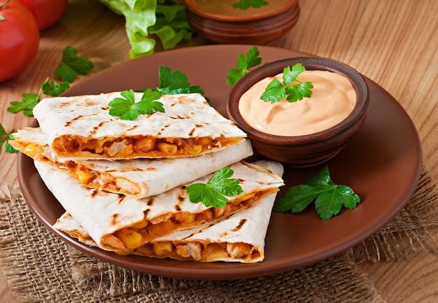 Mexikanischer quesadilla auf dem tisch geschnitten mit gemüse und soßen