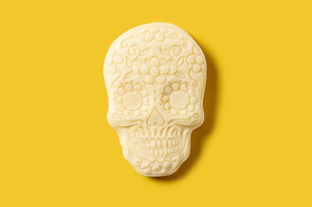 Mexikanischer schädel aus weißer schokolade auf gelbem hintergrund