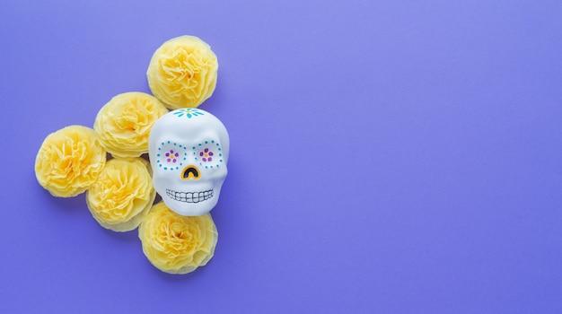 Mexikanischer schädel mit gelben blumen von papiercempasuchil auf veilchen