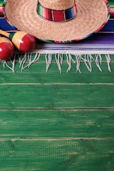 Mexikanischer sombrero, maracas und decke auf grünen brettern