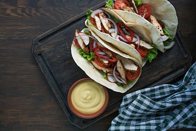 Mexikanischer teller eingewickelter burrito mit hühner- und gemüsenahaufnahme auf einem hölzernen hintergrund. platz für text.