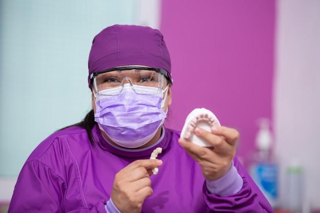 Mexikanischer zahnarzt, der modell zeigt und lächelt