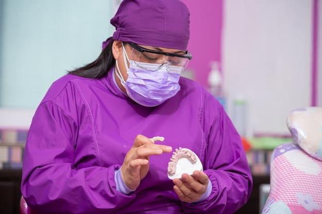 Mexikanischer zahnarzt, der modell zeigt und mit gesichtsmaske lächelt