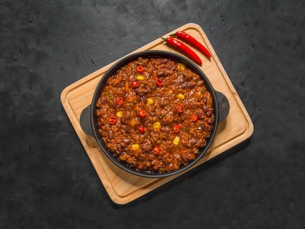 Mexikanisches chili. chili con carne in der pfanne auf schwarzem tisch.