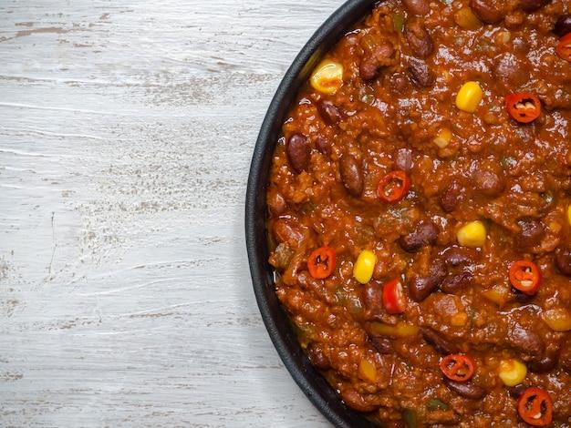 Mexikanisches chili. chili con carne in der pfanne auf weißem holztisch.