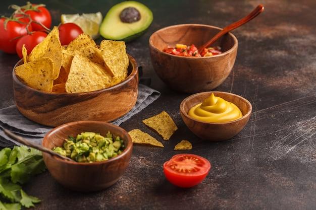 Mexikanisches essen-konzept. nachos - gelbe maistotoposchips mit verschiedenen soßen in den hölzernen schüsseln: guacamole, käsesoße, pico del gallo, kopienraum
