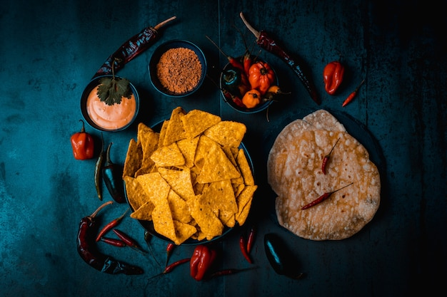 Mexikanisches essen mit nachos-paprika-sauce guacamole-käse auf dunklem hintergrund