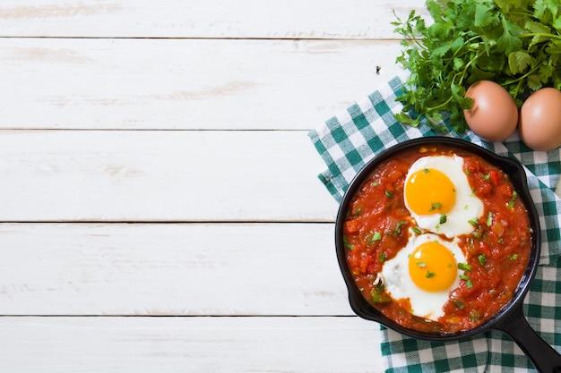 Mexikanisches frühstück, huevos-rancheros in der eisenbratpfanne auf weißer hölzerner tischplatteansicht