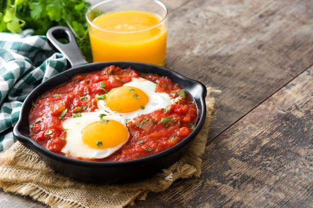 Mexikanisches frühstück huevos rancheros in der eisenpfanne auf holztisch