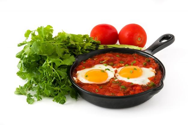 Mexikanisches frühstück huevos rancheros in der eisenpfanne lokalisiert auf weißem hintergrund