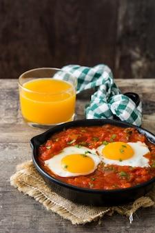 Mexikanisches frühstück: huevos rancheros in eiserner pfanne auf holztisch