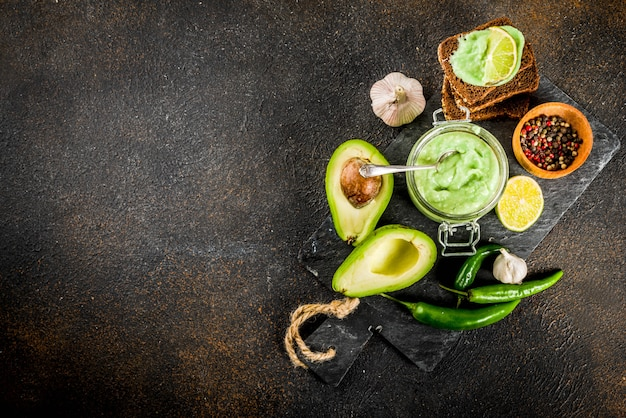 Mexikanisches lebensmittel, guacamole mit roggentoastsandwichen auf dunklem hintergrund, kopienraum