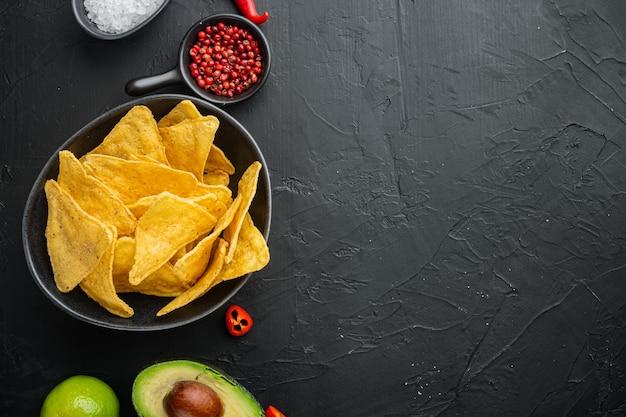 Mexikanisches lebensmittelkonzept. nachos - gelbe mais-totopos-chips mit verschiedenen saucen, auf schwarzem tisch, draufsicht oder flachem laien