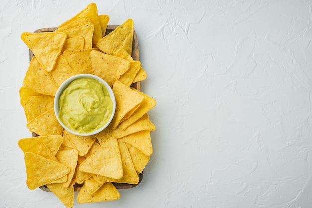 Mexikanisches lebensmittelkonzept. nachos - gelbe mais-totopos-chips mit verschiedenen saucen, auf weißem tisch, draufsicht oder flachem laien