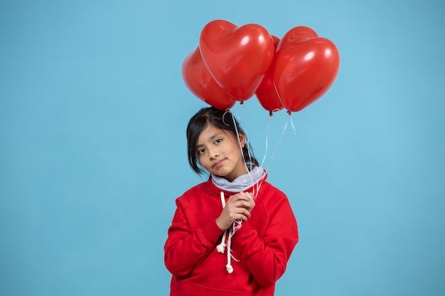 Mexikanisches mädchen, das einen bündel des roten herzballons hält