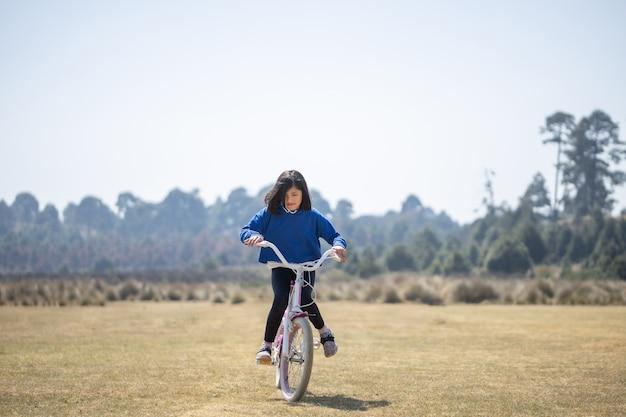 Mexikanisches mädchen lernt fahrrad fahren im freien