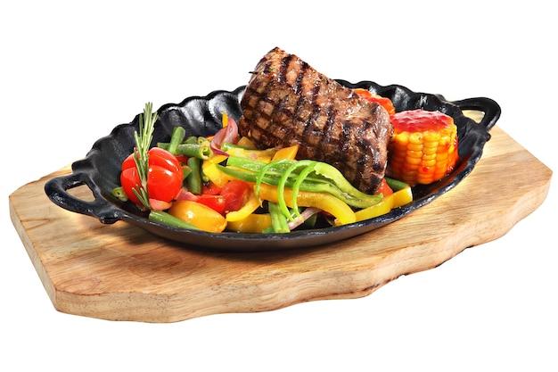 Mexikanisches steak im ovalen servierteller aus gusseisen mit griffen auf holzteller, lokalisiert auf weißem hintergrund.