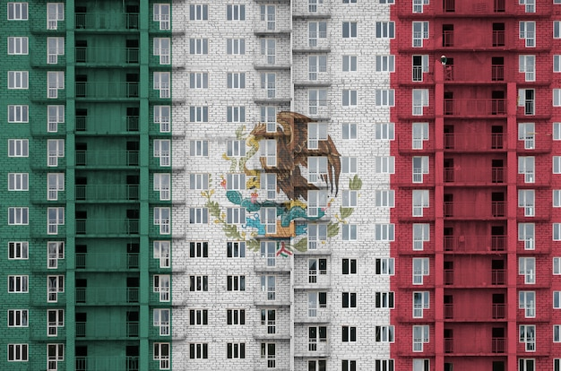 Mexiko-flagge in den farben auf dem im bau befindlichen mehrstöckigen wohngebäude dargestellt.
