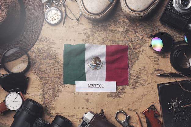 Mexiko-flagge zwischen dem zubehör des reisenden auf alter weinlese-karte. obenliegender schuss